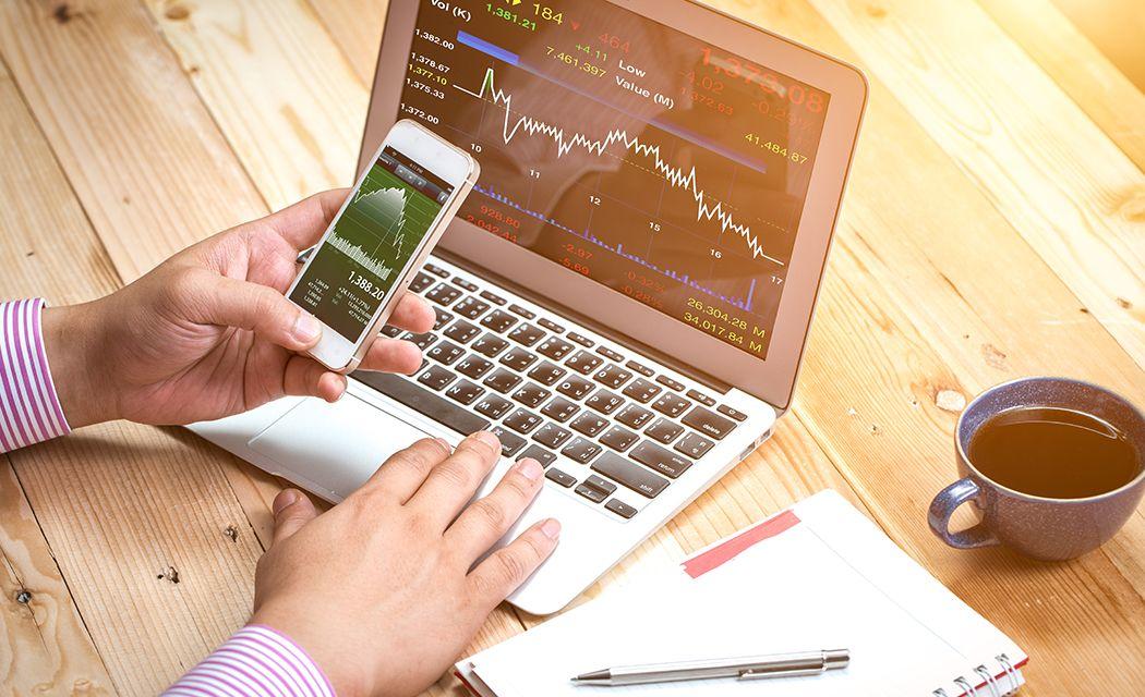 notebook a telefón s otvorenými grafmi pre obchodovanie na burze