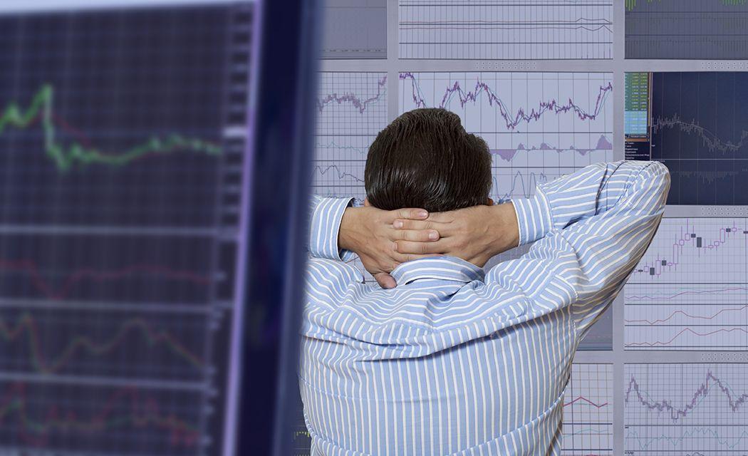 Zamyslený obchodník nad otázkou, ako dosiahnuť ziskové obchodovanie na burze